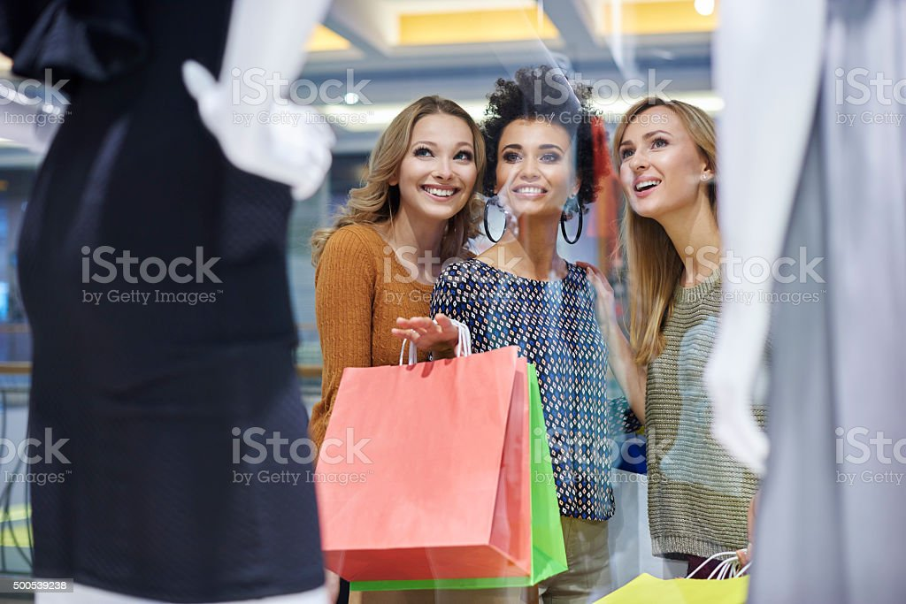 Best friends looking at window display stock photo