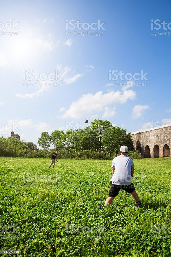 Best friends playing football at park stock photo