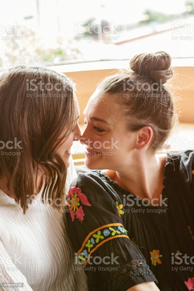 Best friends rubbing noses playfully in a pub stock photo