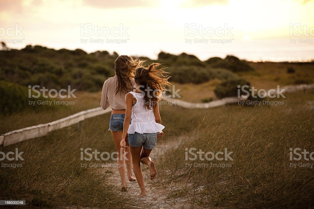 Best friends running together into the sunset royalty-free stock photo