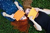 Meilleurs amis étudiants se cachent derrière des visages des cahiers pour prendre notes.