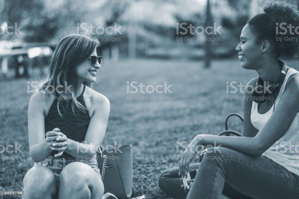 Best friends talking at riverbank stock photo