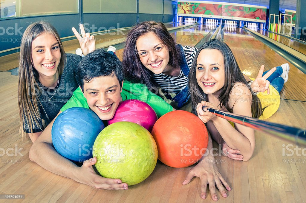 Best friends using selfie stick taking pic on bowling track stock photo
