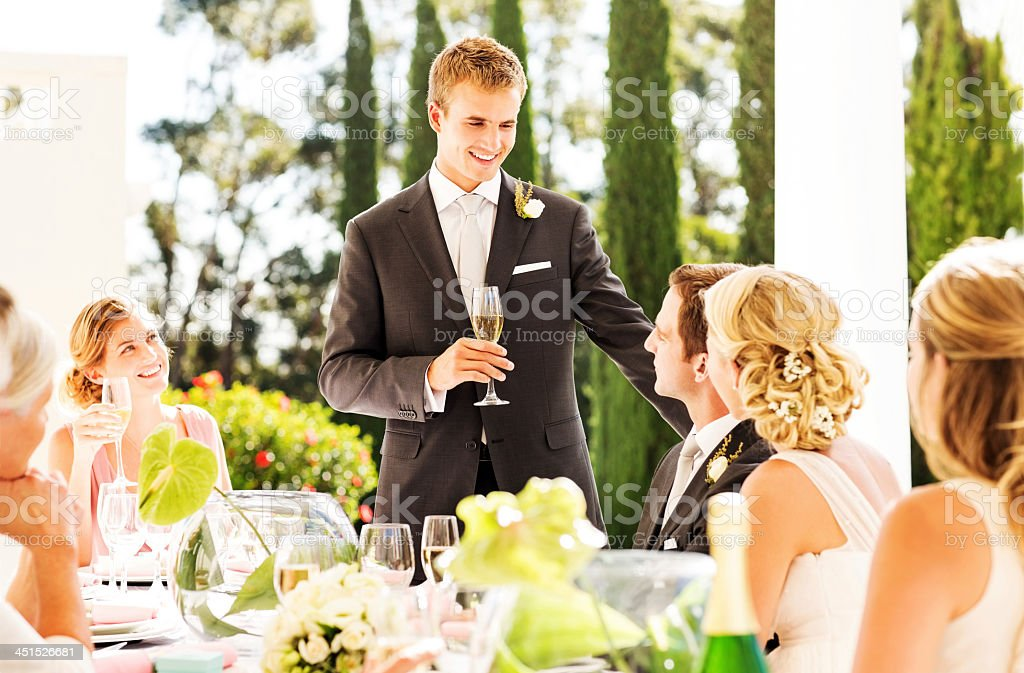 Best Man Looking At Couple While Giving Speech During Reception stock photo