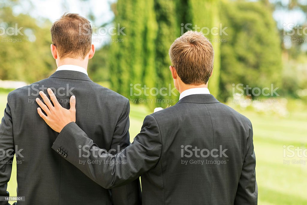 Best Man Standing With Hand On Groom's Back In Garden stock photo