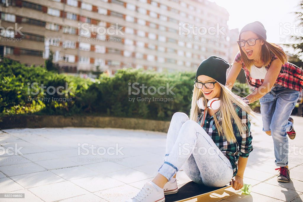 Besties having fun on longboard in city stock photo