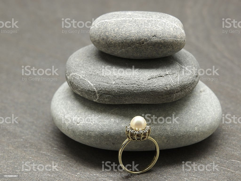 Betrothal ring and pebble stones royalty-free stock photo