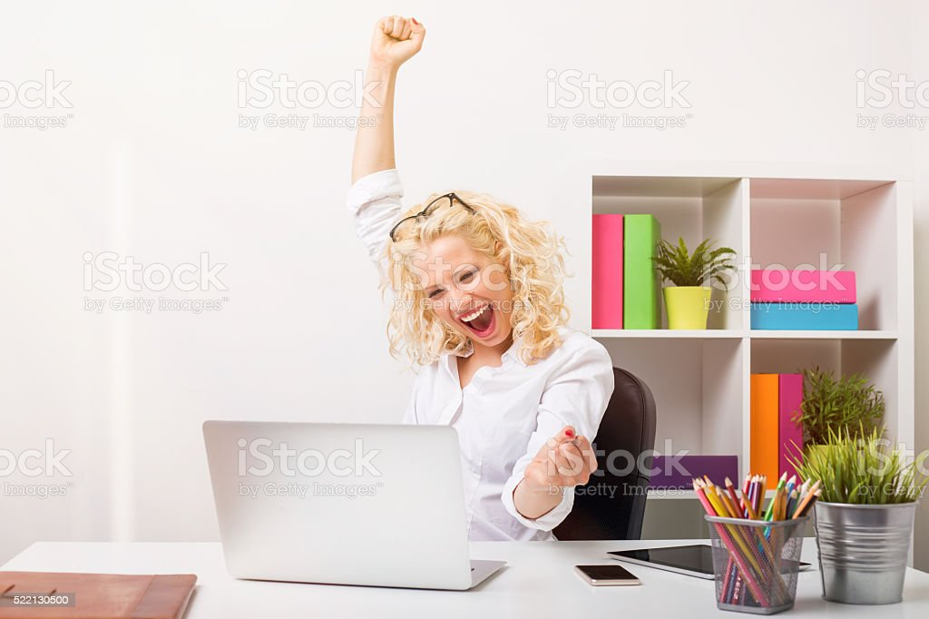 Beuatifull woman at the office celebrating her success stock photo
