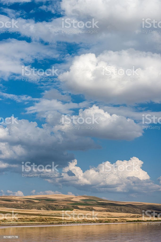 Beutiful cloudscape with small hills and the lake foreground stock photo