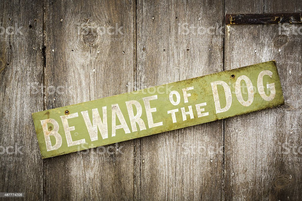 Beware Of Dog Sign on Old Worn Wood Fence stock photo