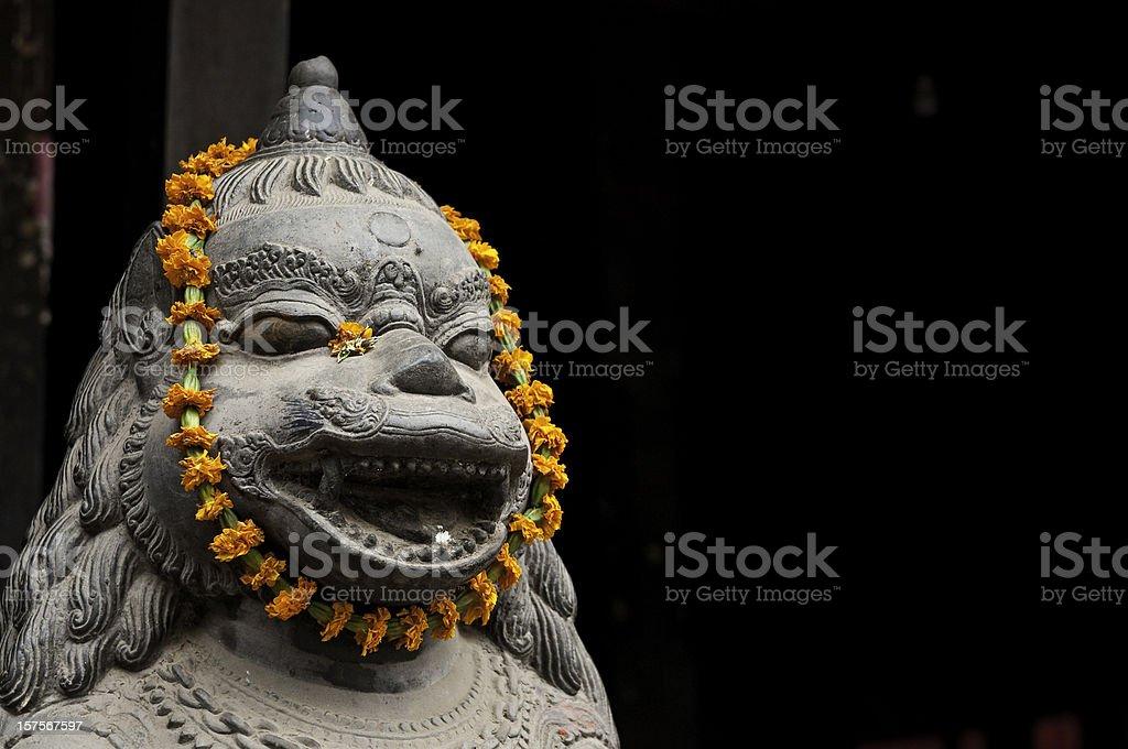 Bhuddist shrine orange marigold flower garland stone lion Kathmandu Asia stock photo