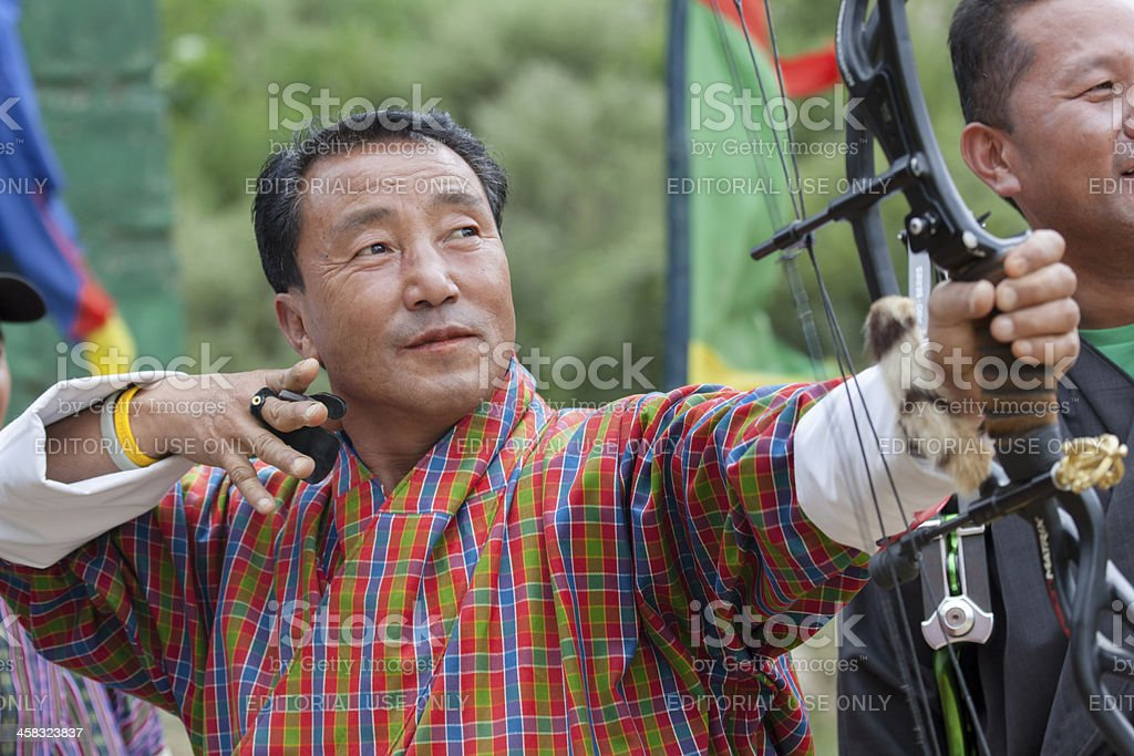 Bhutanese archer releases arrow in archery competition royalty-free stock photo