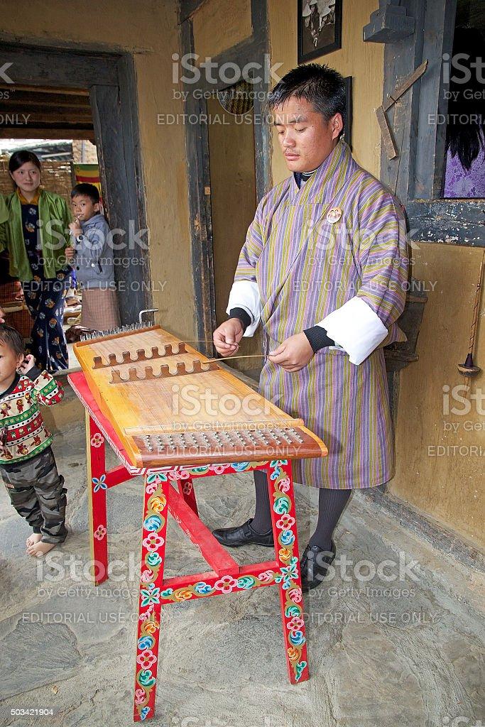 Bhutanese musician is playing a yangqin, Bhutan stock photo