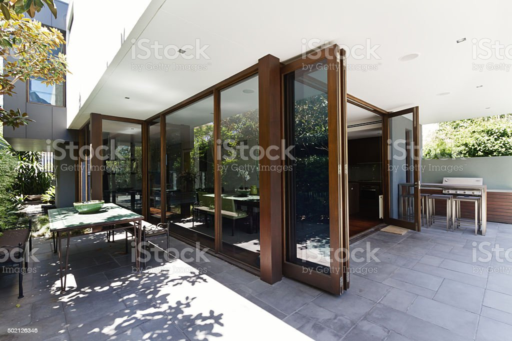 Bi fold doors opening to rear courtyard of contemporary home stock photo
