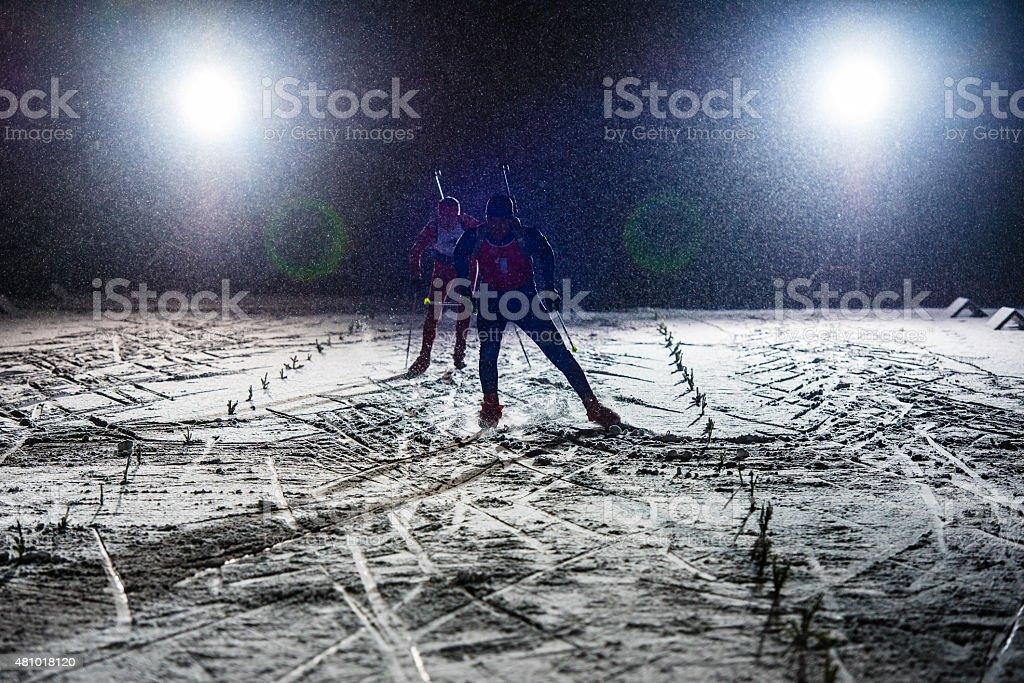 Biathlon athletes skiing stock photo