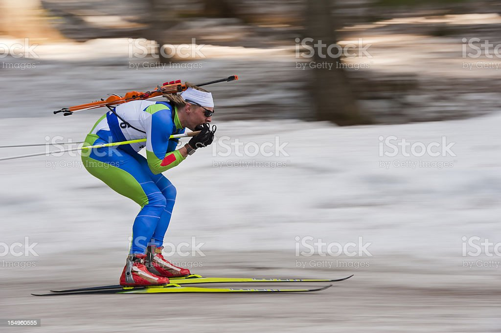 Biathlon competitor at downhill stock photo