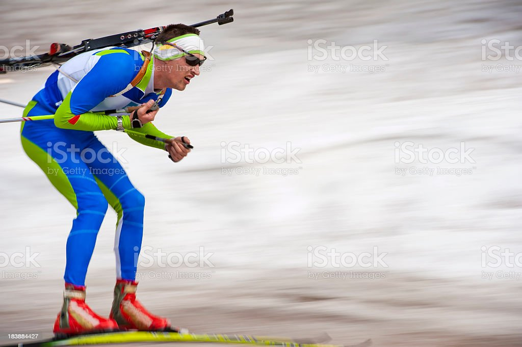 Biathlon competitor at downhill stock photo