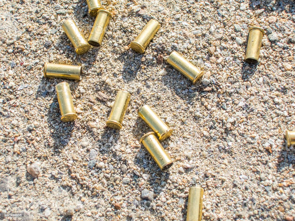 biathlon rifle scattered fired cartridges shining in the sun stock photo
