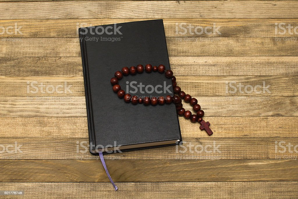 bible book and rosary  on dark wood planks stock photo