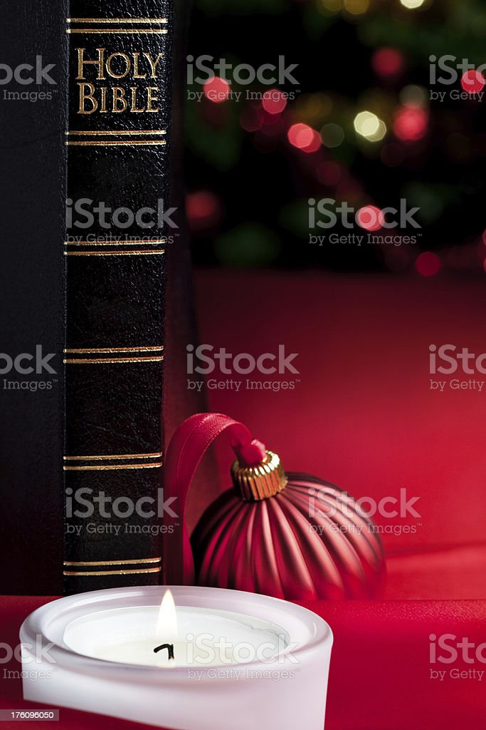 Bible, candle light and defocused lights stock photo