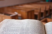 Bible open in a church with wooden chairs