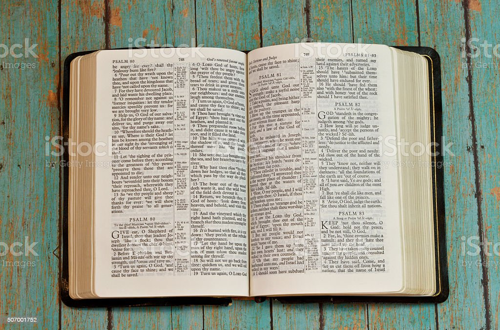 Bible Opened to Psalm on wooden plank background stock photo