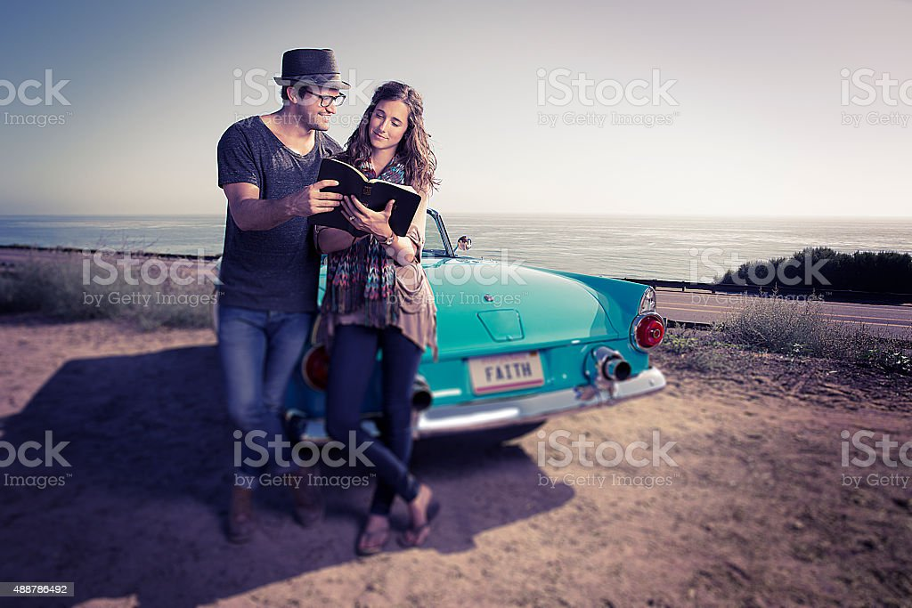 Bible Reading Couple by a Blue Convertible stock photo