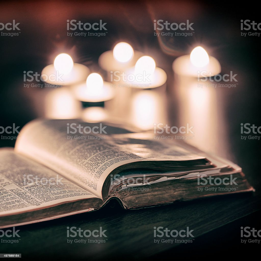 Bible with candles stock photo