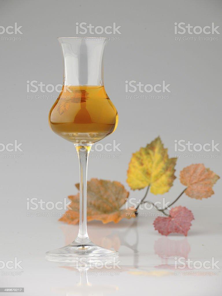 Bicchiere di Vin Santo su fondo neutro con foglie Vite stock photo
