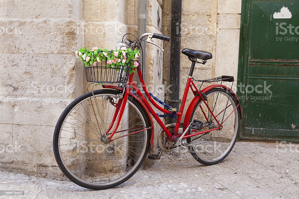 Bicycle and basket covered in flowers leaning on stone wall stock photo