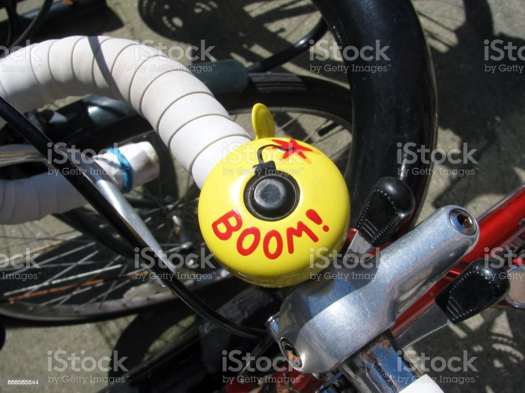 Bicycle bell painted yellow with hand written word Boom stock photo
