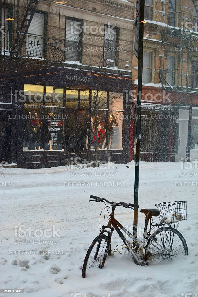 bicycle covered in snow on a sidewalk in new york stock photo