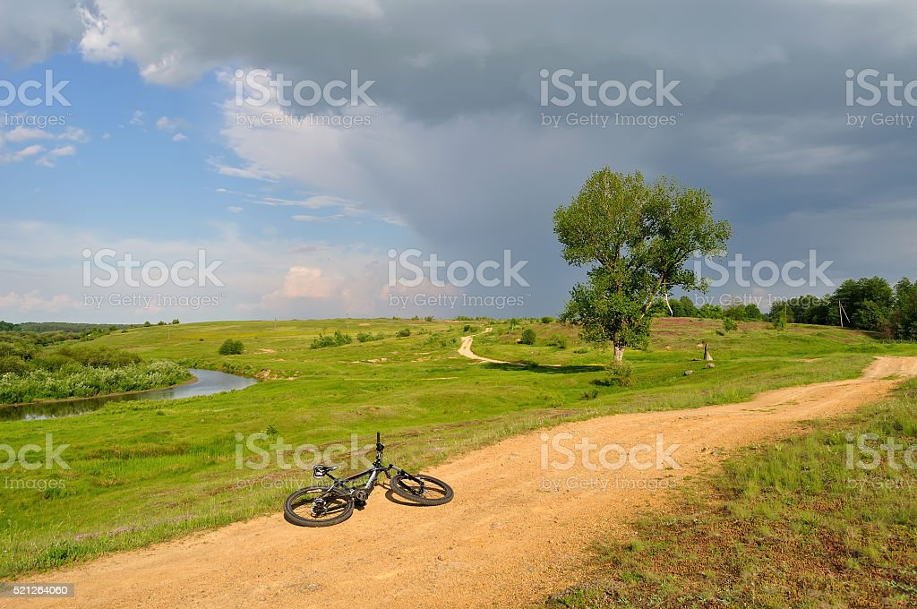 bicycle lying near the river stock photo