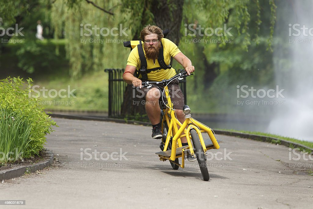 Bicycle messenger with cargo bike speeding stock photo