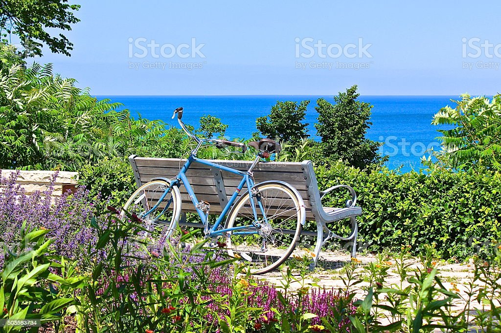 Bicycle, park bench and flowers overlooking lake stock photo