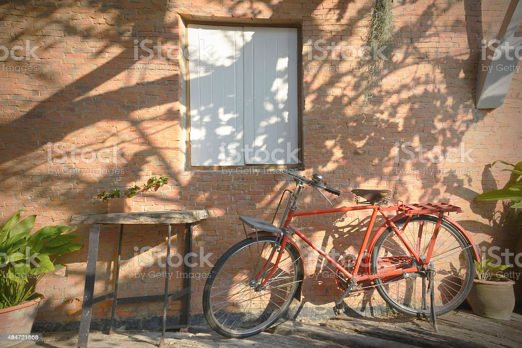Bicycle parking under the shade beside the wall royalty-free stock photo