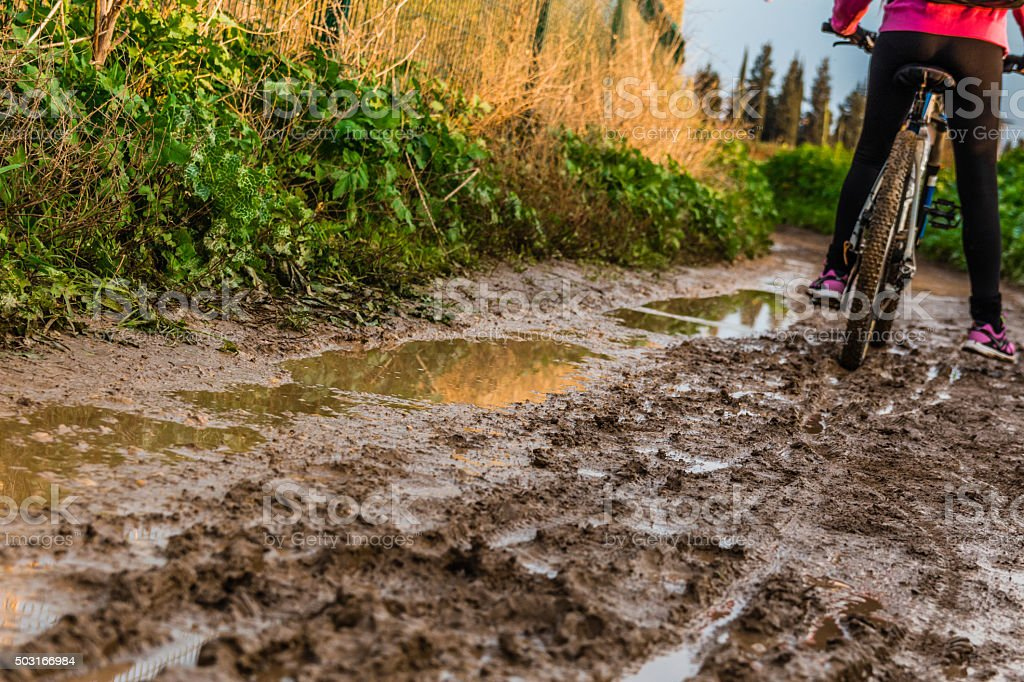 Bicycle ride through muddy dirt road stock photo
