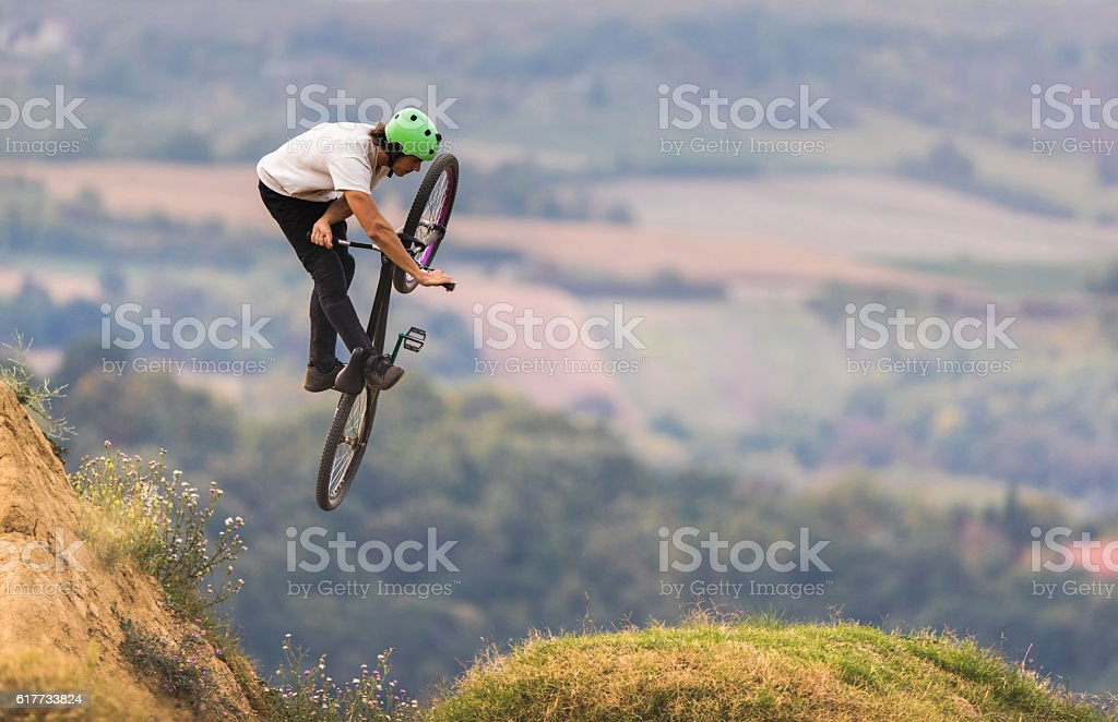 Bicycle rider doing invert move while being in mid air. stock photo