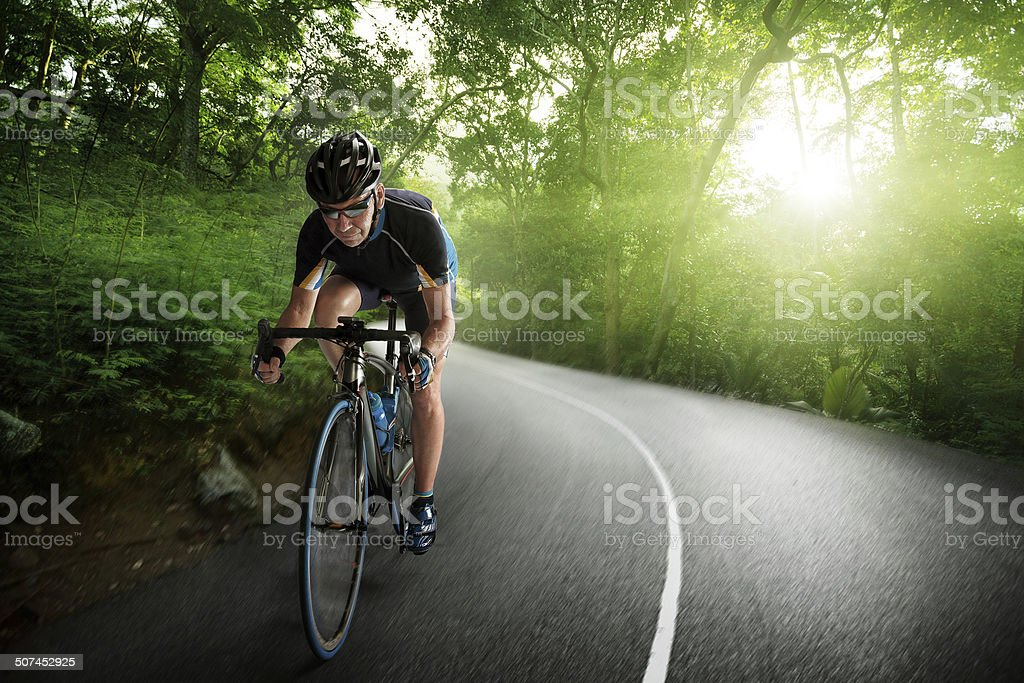 Bicycle Rider pedaling on a Forest Highway stock photo