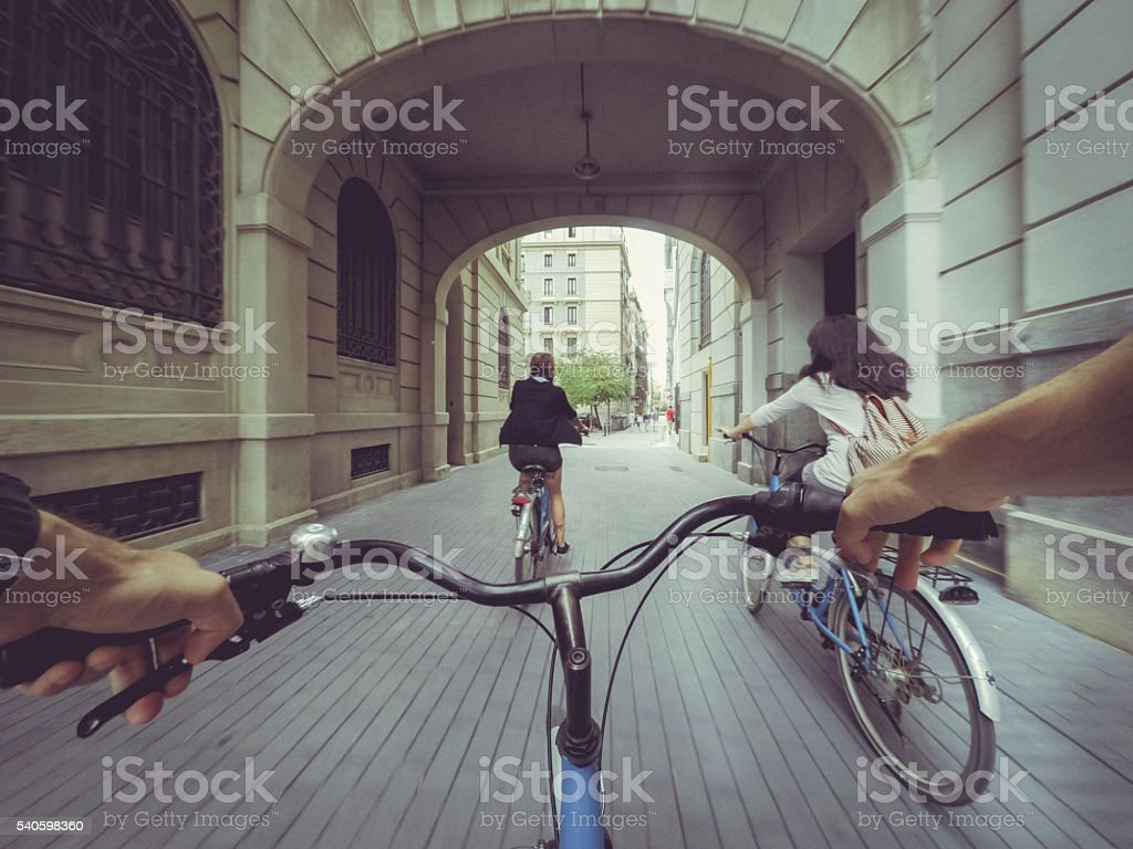 POV bicycle riding with two girls in the city stock photo