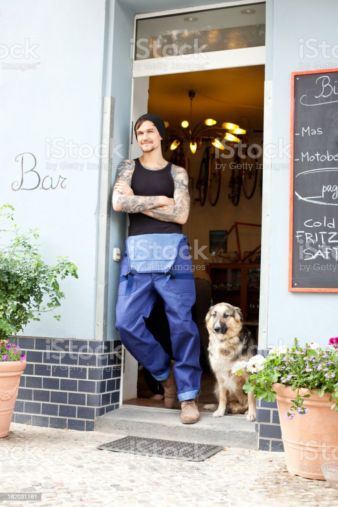Bicycle shop owner or mechanic with dog stock photo