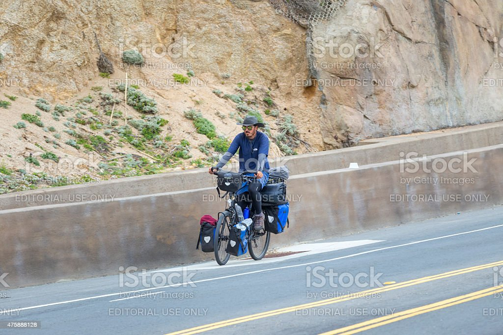 Bicycle tourist with loaded bike riding on highway one stock photo