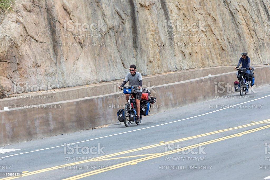 Bicycle tourists with loaded bike riding on highway one stock photo