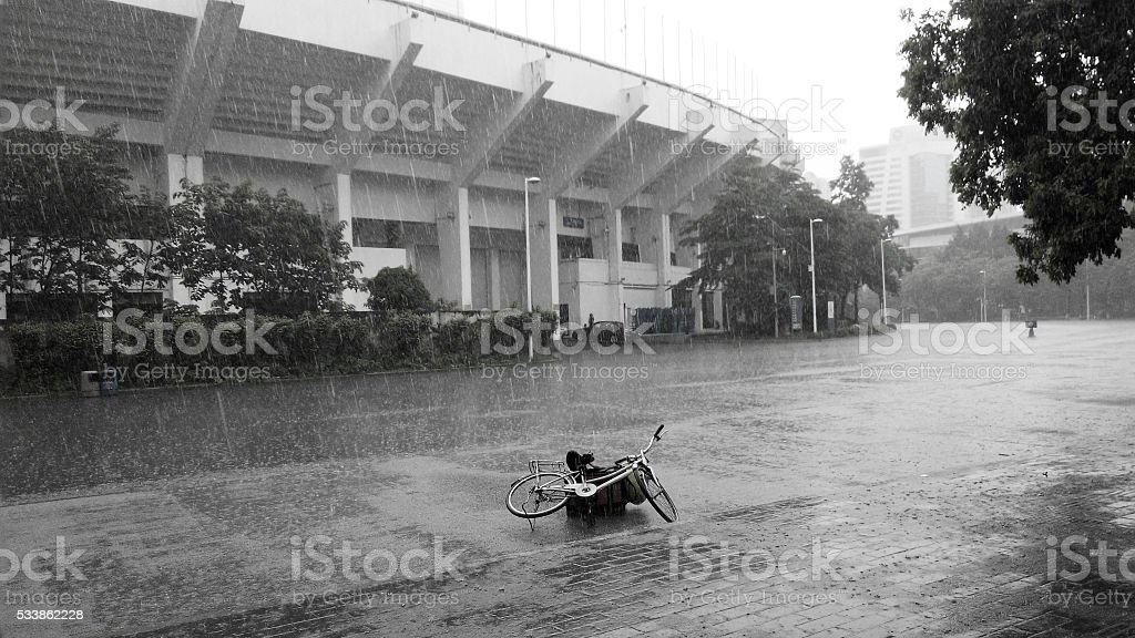 Bicycle under the heavy rain stock photo