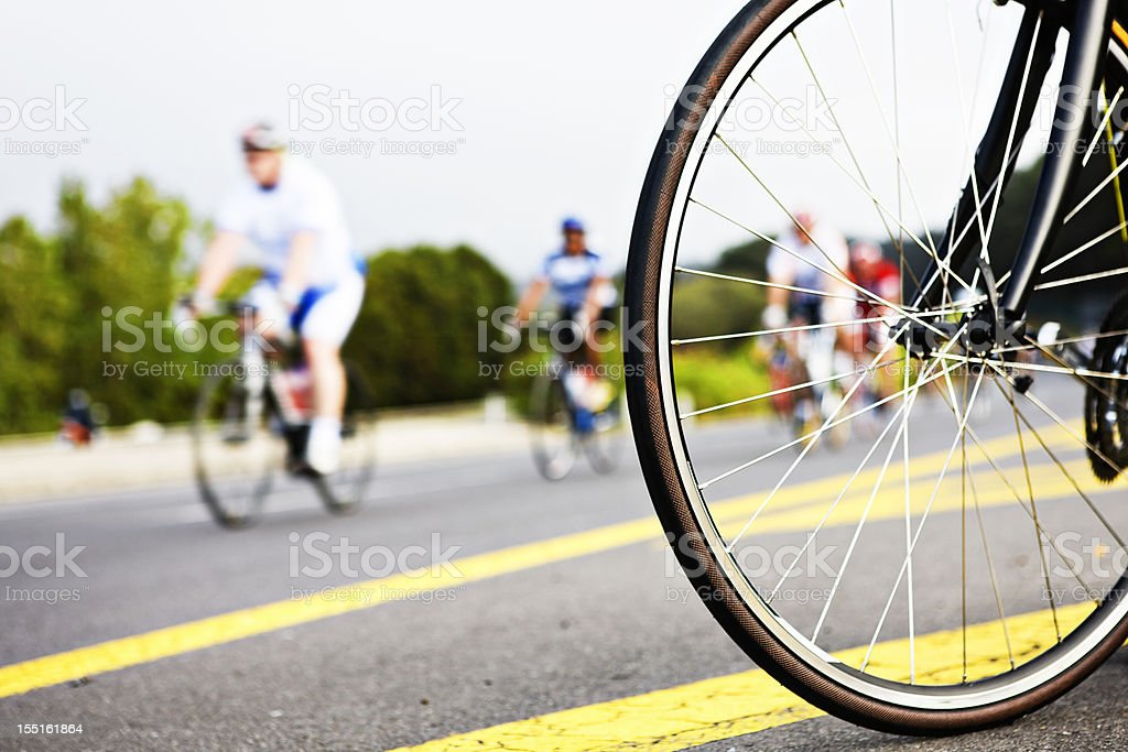 Bicycle wheel with motion-blurred racing cyclists in background royalty-free stock photo