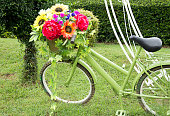 bicycle with basket full of flowers standing in the  grass