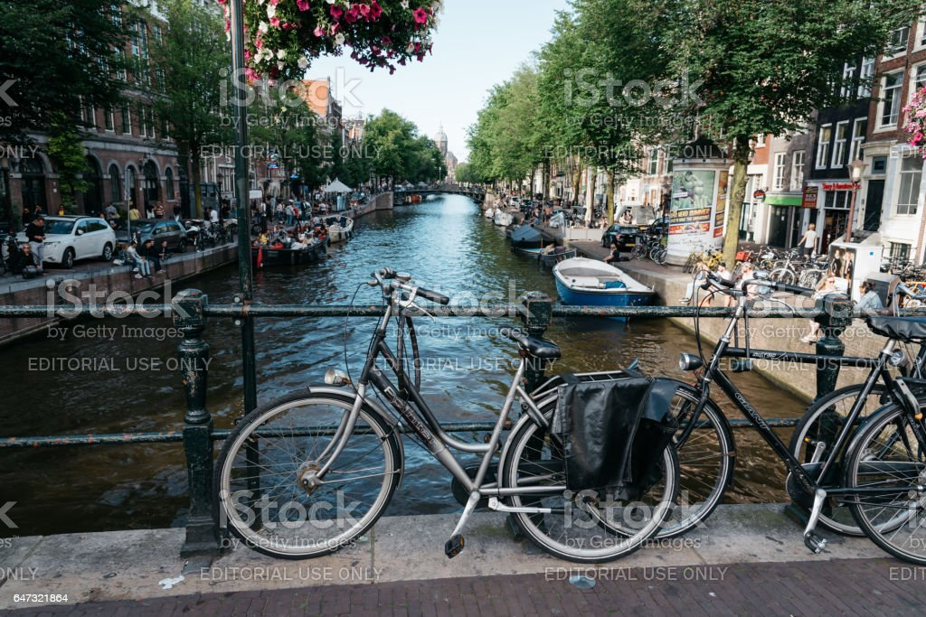 Bicycles in a bridge over the canals of Amsterdam. stock photo