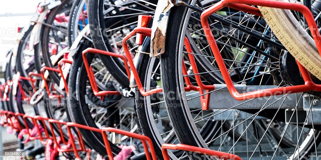 Bicycles in bicycle parking rack at train station in Holland stock photo