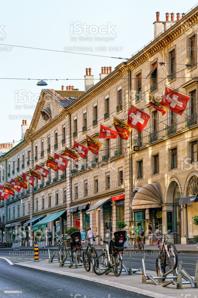 Bicycles in Rue Corraterie Street with flags in Geneva Swiss stock photo
