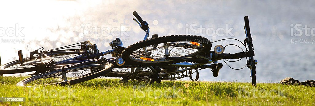 bicycles lying in the grass near a lake stock photo
